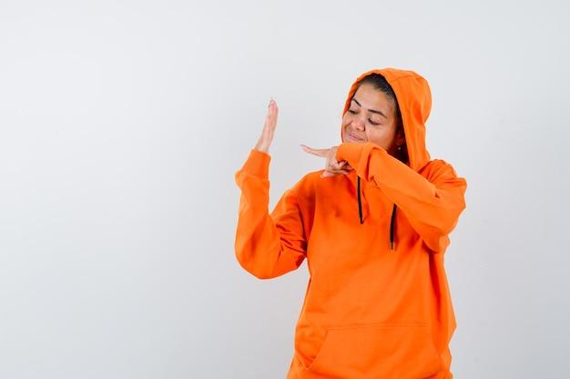 オレンジ色のパーカーで彼女の空の手のひらを指して、自信を持って見える女性