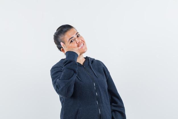 パーカーで彼女の歯を指して、陽気に見える女性。正面図。