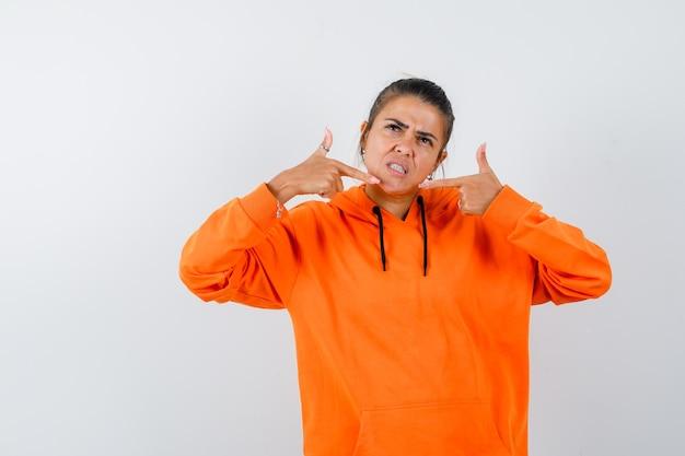 オレンジ色のパーカーで自分を指差して自信を持って見える女性