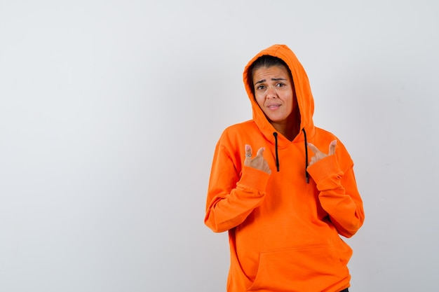 オレンジ色のパーカーで自分を指差して困惑している女性