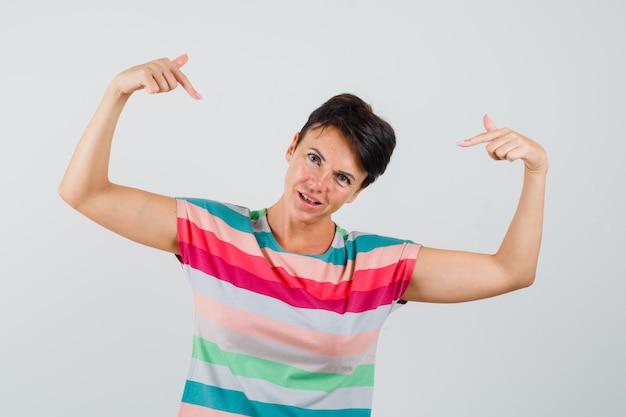 Женщина указывает на себя в полосатой футболке и выглядит гордо. передний план.