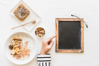Female pointing finger at blank small blackboard with healthy breakfast; honeycomb and nuts