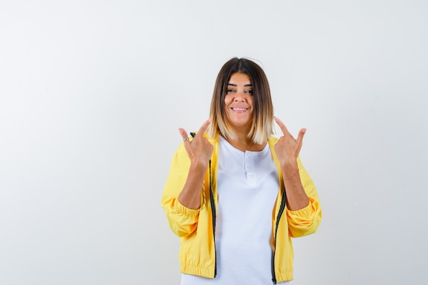 Donna che punta a se stessa in t-shirt, giacca e guardando fiducioso, vista frontale.