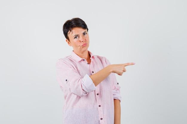 Женщина в розовой рубашке указывает на правую сторону и выглядит разумной. передний план.
