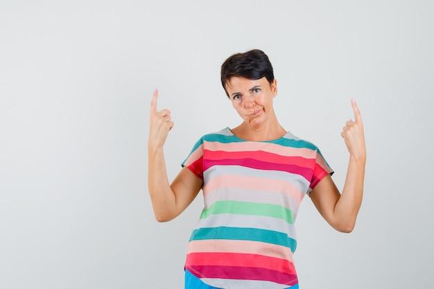 여성 스트라이프 티셔츠를 가리키고 주저하고 있습니다. 전면보기.