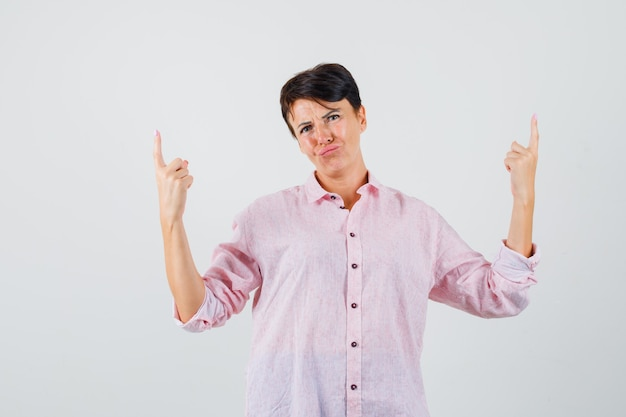 Female pointing up in pink shirt and looking hopeless , front view.