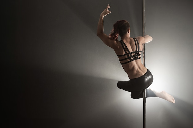 Female pole dancer dancing on a black