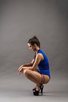 灰色の背景に青いボディスーツとハイヒールを身に着けている女性のポールダンサー