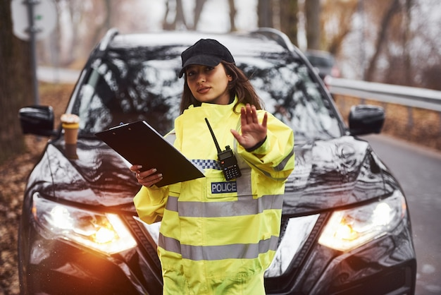 Female police officer in green uniform standing with radio transmitter and notepad against car.