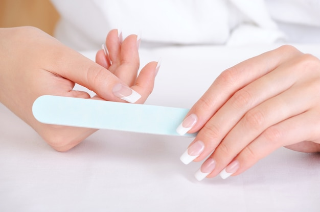 Female polishing  her thumb using the nailfile