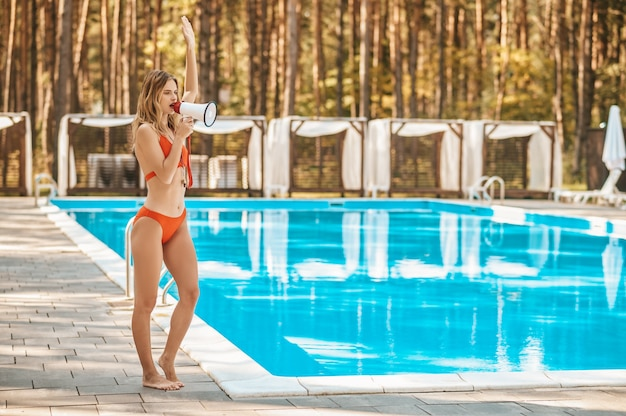 A female pool lifeguard with a loudspeaker near the pool