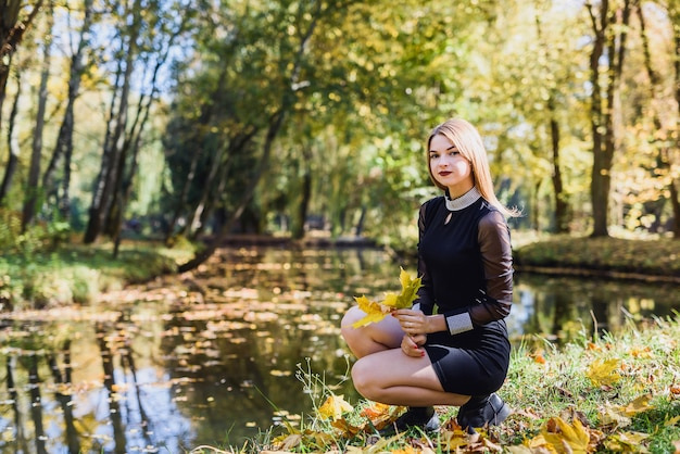 Female porteait in autumn park. beaurtiful woman in black dress posing with yellow trees