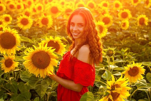 일몰 광선에 피는 해바라기 밭에서 젊은 여자의 여성 초상화 코카서스의 귀여운 소녀...