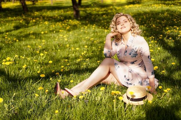 屋外の女性の肖像画。花畑で麦わら帽子をかぶった女性。国の夏