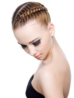 ピグテールの美しい髪型を持つ女性の肖像画。白で隔離