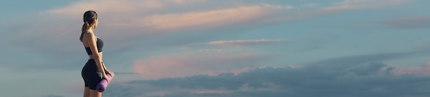 Женщина позирует в спортивной одежде на фоне неба. средняя часть тела.