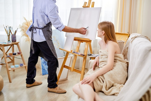 Female posing for portrait, professional painter drawing portrait of young lady in studio