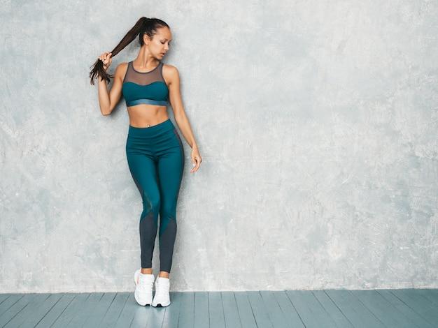 Female posing in studio near gray wall
