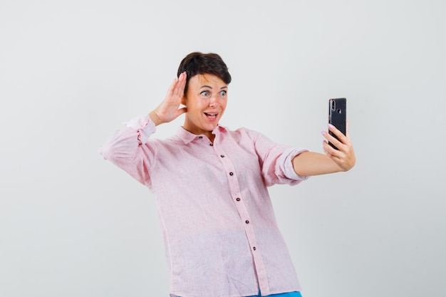 핑크 셔츠에 화상 통화를하고 쾌활한 찾고있는 동안 포즈를 취하는 여성. 전면보기.