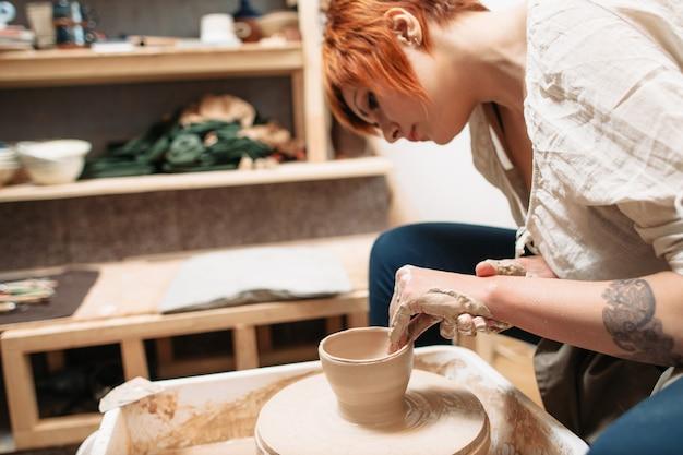 Женщина-гончар тщательно лепит глиняную чашу