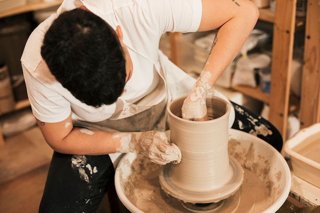 Female potter clinging the pot on pottery wheel in the workshop