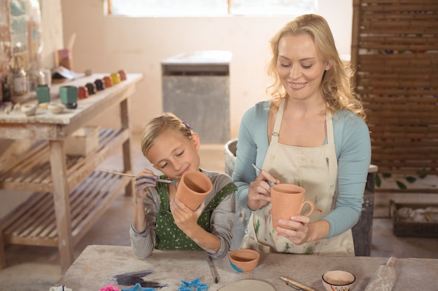 Female potter and girl painting in pottery workshop
