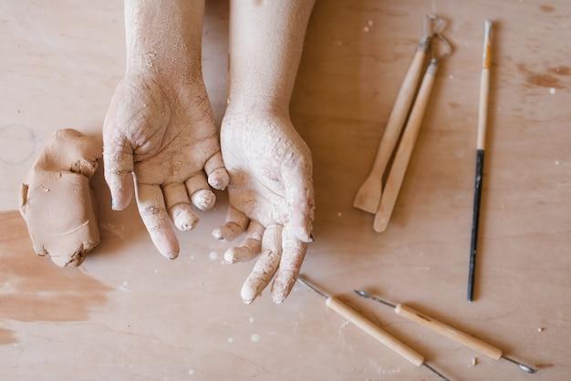 乾燥した粘土で覆われた女性の陶芸家の手