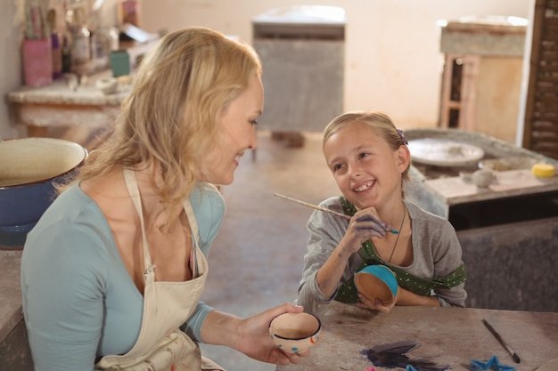 Female potter interacting with girl in pottery workshop