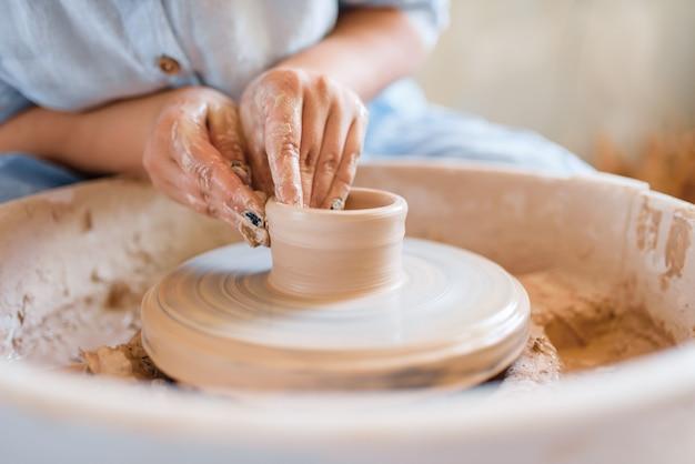 ろくろで鍋を作る女性の陶芸家。ボウルを成形する女性。