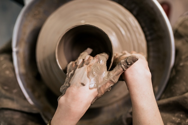 Женский гончар делает глиняную посуду на прялке.