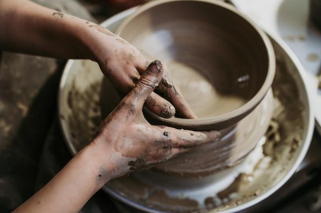 Женщина-гончар делает глиняную посуду на прялке