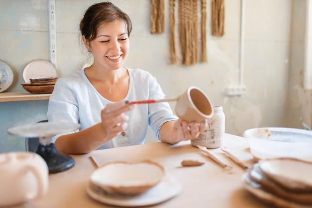 Гончарша расписывает горшок, гончарную мастерскую.
