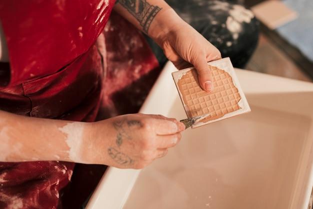 浴槽の上の鋭い道具で塗料を取り除く女性の陶工