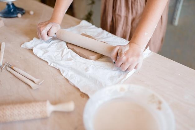 女性の陶芸家がめん棒で泡を広げます