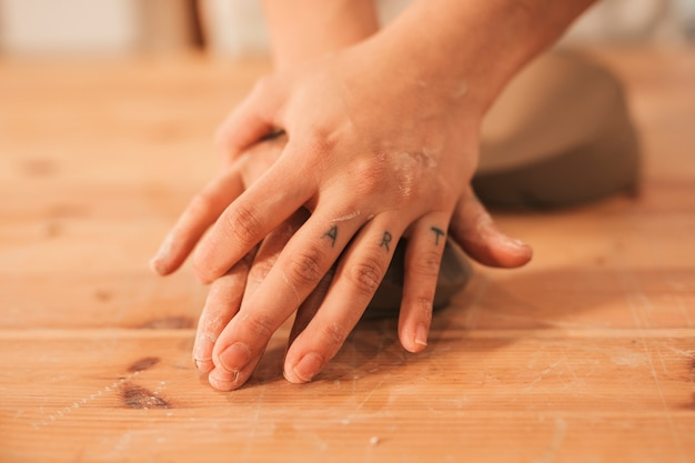 Female potter's hand kneading the clay on wooden surface