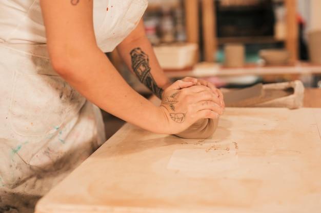 女性の陶工の手がテーブルの上の粘土を混練