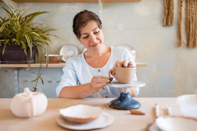 女性の陶芸家の皮鍋、陶器工房。ボウルを成形する女性。