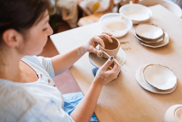 ヘラで女性の陶芸家の皮の鍋