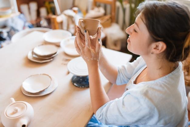 Female potter skins pot with her fingers, pottery workshop.