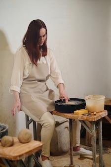 Женщина-гончар работает на гончарном круге в мастерской