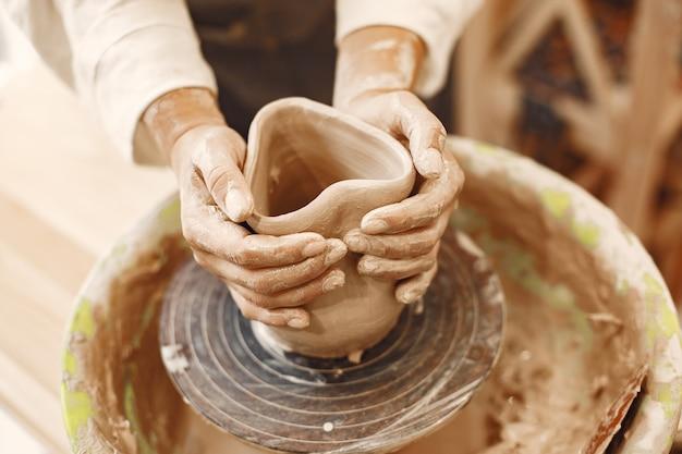 スタジオでホイールの粘土を扱う女性の陶工。ろくろに水が飛び散った粘土。