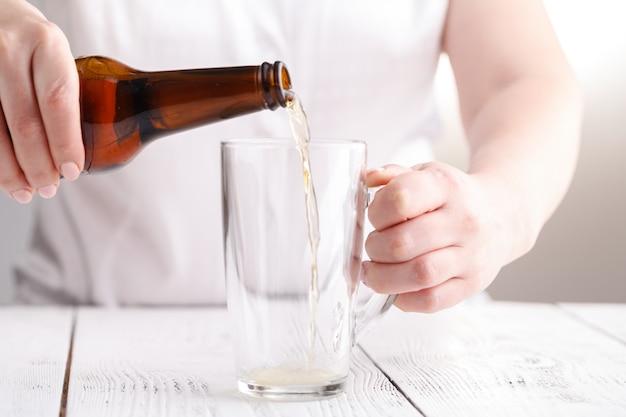 ガラスのマグで女性注ぐビール、コンセプトをリラックス