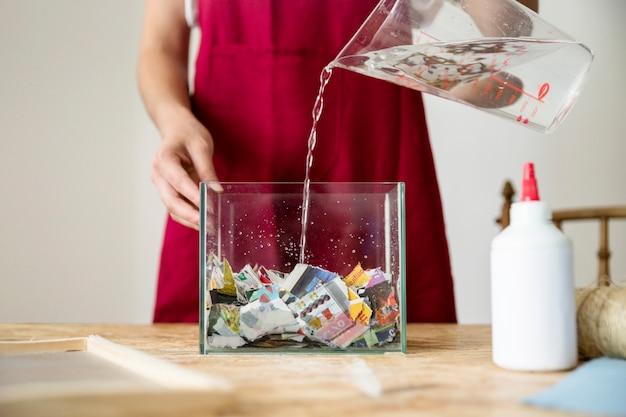 木製の机の上に紙で満たされた容器に水を注ぐ女性