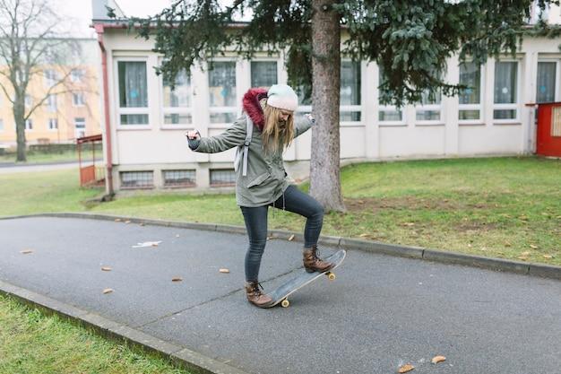 Female practicing on skateboard on walkway