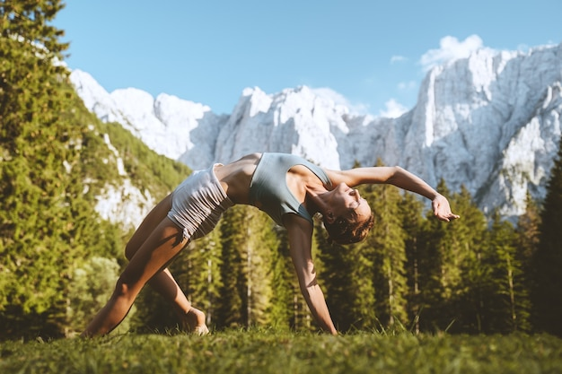 Female practicing yoga on nature young woman doing yoga in mountains