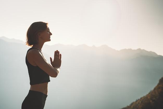 Женщины практикуют йогу на природе молодая женщина медитирует на фоне гор