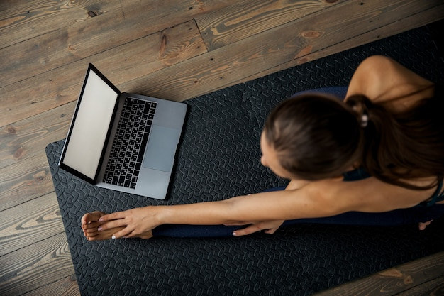 Female practicing yoga or pilates indoors on mat, doing exercises and stretching, watching video lesson online. top view. high quality photo