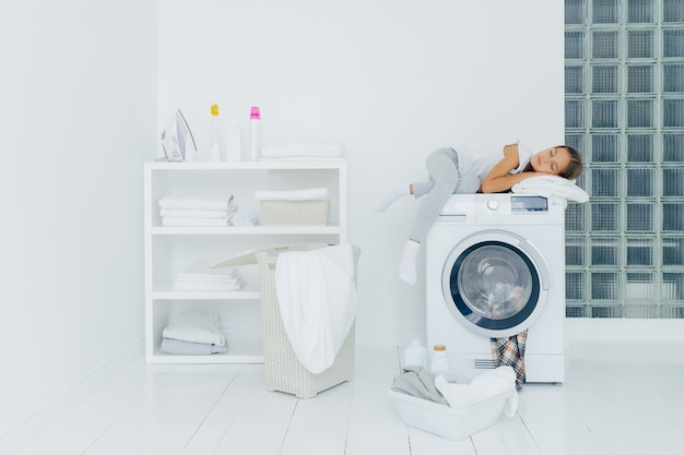 Female preschooler sleeps on washing machine, being tired with washing, poses in white big laundry room with basket and basin full of dirty clothes bottles of liquid powder. childhood, domestic chores