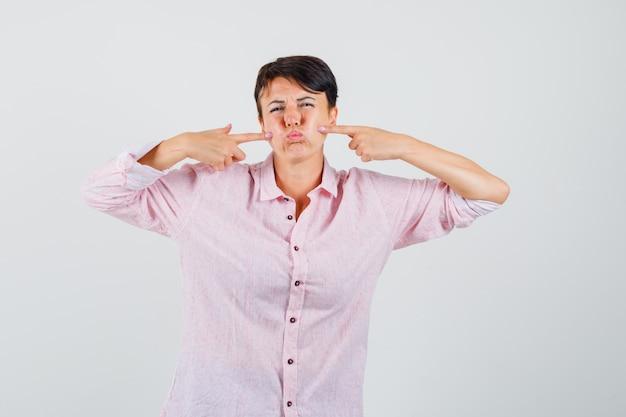Femmina premendo le dita sulle guance soffiate in vista frontale camicia rosa.
