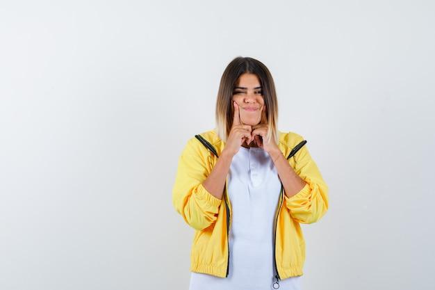 Donna che preme le dita sulle guance in t-shirt, giacca e sembra felice. vista frontale.